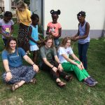 Local children braiding hair of short term missionaries on mission trip