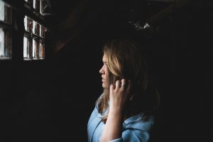 Woman looking out of a dark room through a window. Pondering which opinions are the most valuable opinions.